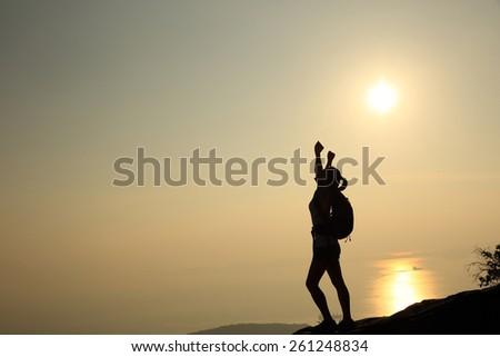 cheering woman hiker open arms at sunset mountain peak - stock photo