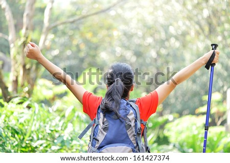 cheering woman hiker open arms in jungle