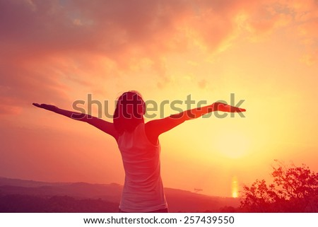cheering woman open arms mountain peak - stock photo