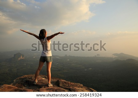 cheering woman open arms mountain peak - stock photo
