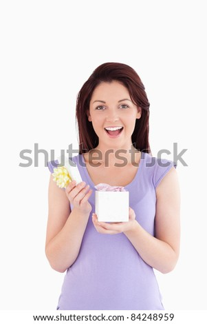Cheering woman opening a box in a studio