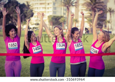 Cheering women supporting breast cancer marathon in parkland - stock photo