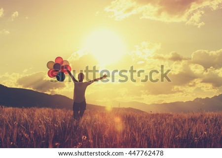 cheering young asian woman running on sunset grassland with colored balloons - stock photo