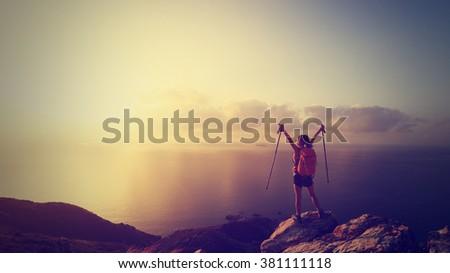 cheering young woman backpacker at sunrise seaside mountain peak - stock photo