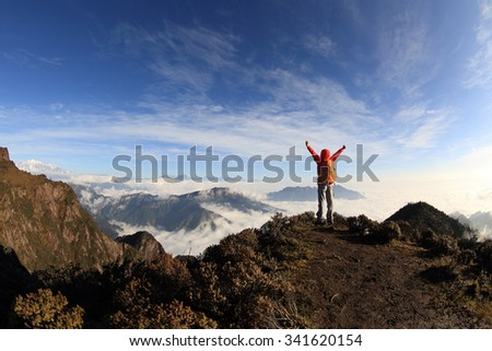 cheering young woman hiker open arms on mountain peak - stock photo