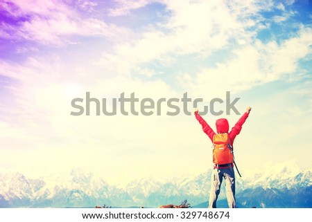 cheering young woman hiker open arms to beautiful snow mountain on peak - stock photo