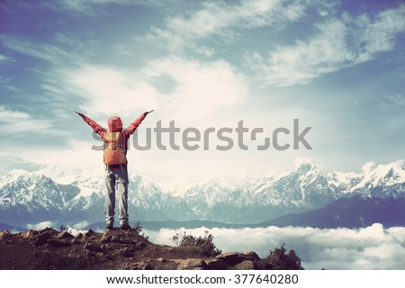cheering young woman hiker open arms to beautiful snow mountain summits - stock photo