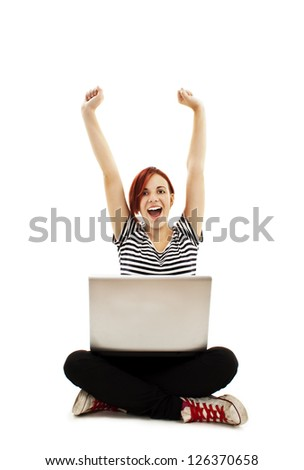 Cheering young woman sitting cross-legged while surfing the internet. Isolated on white background - stock photo