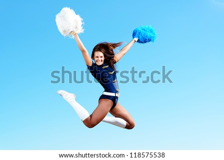 cheerleader girl jumping on a background of blue sky