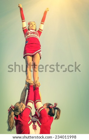 Cheerleaders in action on a vintage filtered look - Concept of unity and team sport - Training at college high school with young female teenagers - stock photo