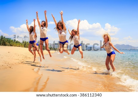 cheerleaders in white blue uniform jump over shallow water lift hands and smile against azure sea wind shakes hair
