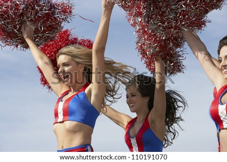 Cheerleaders running together with pompoms against clear sky - stock photo