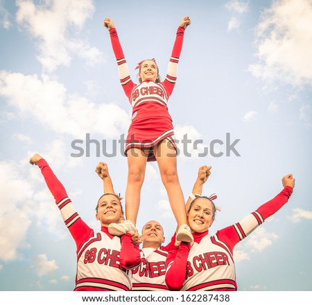 Cheerleaders team with male Coach - stock photo