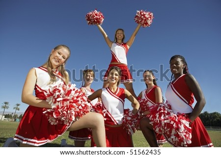 Cheerleading squad in formation on field, portrait, (portrait) - stock photo