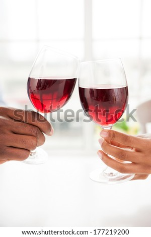 Cheers! Close-up of couple holding wineglasses and toasting - stock photo