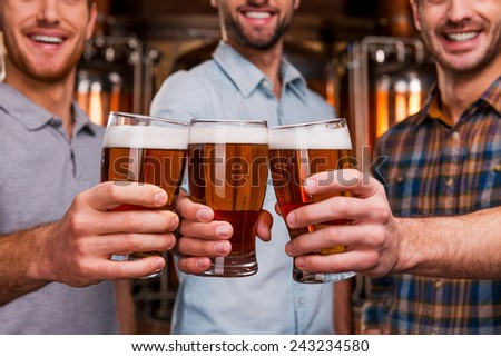 Cheers! Close-up of three cheerful young men in casual wear stretching out glasses with beer and smiling while standing in front of metal containers - stock photo