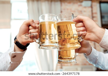 Cheers. Close-up of three cups with beer stretched out by businessmen in the pub - stock photo