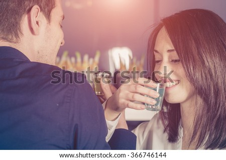 Cheers! Couple in love is drinking alchool togheter in a shot glass during a party - caucasian people - people, drink, party and lifestyle concept - stock photo