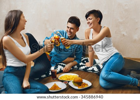 Cheers. Group Of Happy Smiling Young People Toasting Beer Bottles And Eating Fast Food. Friends Partying At Home, Sitting On The Floor. Celebration, Friendship, Leisure, People Concept