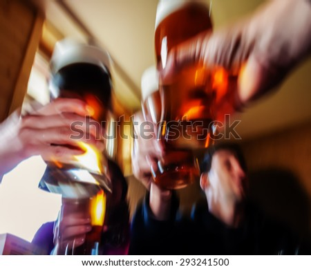 cheers! - hands with glass of beer in abstract motion blurred scene - stock photo