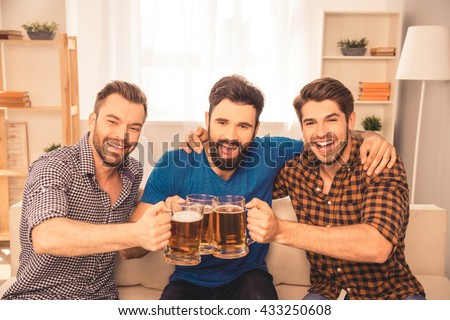 cheers! Handsome men celebrating victory of favorite team and clinking glass of beer at home - stock photo