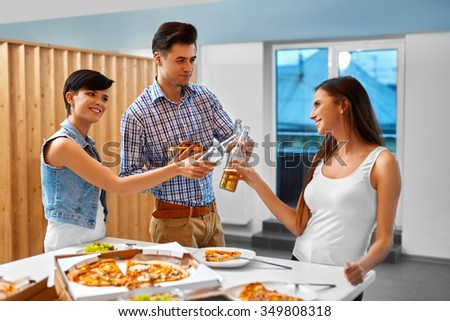 Cheers. Happy Friends Having Fun, Eating Pizza And Cheering With Beer Bottles Indoors. Young Cheerful People Having Dinner Party At Home. Holiday Celebration.  Friendship, Leisure, Fast Food Concept. - stock photo