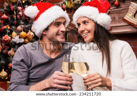 Cheers! Happy young loving couple in Santa hats bonding to each other and cheering with wine and with Christmas Tree in the background  - stock photo