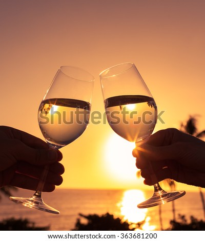 Cheers in a beautiful beach setting.  - stock photo