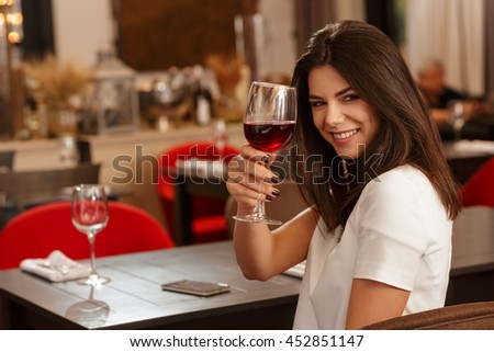 Cheers! Shot of a stunning elegant young woman cheering to the camera with her glass of wine smiling joyfully over her shoulder