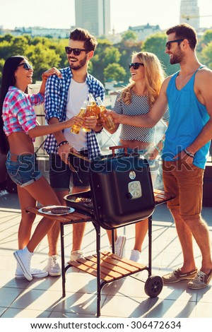 Cheers to friends! Full length of fourjoyful young people clinking glasses with beer and barbecuing while standing on the roof - stock photo