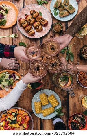 Cheers to friends! Top view of four people cheering with wine while sitting at the rustic dining table - stock photo