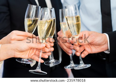 Cheers to success. Close-up of business people holding flutes with champagne - stock photo