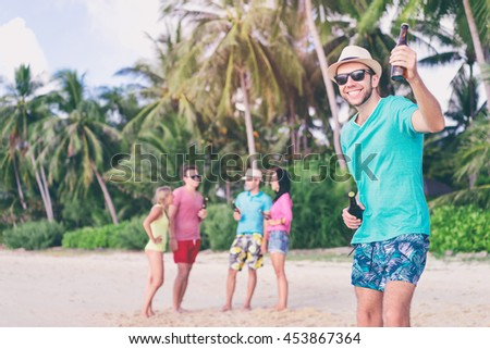 Cheers! Welcome to the beach party. Group of young people drinking beer together on the sea shore. - stock photo