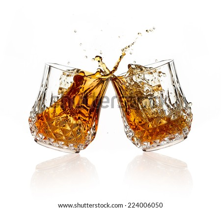 Cheers. Whiskey toast. Two glasses clicking together over white background. Splashing whiskey on glasses of cut glass - stock photo