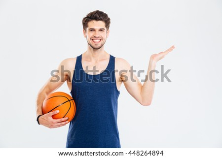 Cheerul young sportsman with basketball ball holding copyspace on palm over white background - stock photo