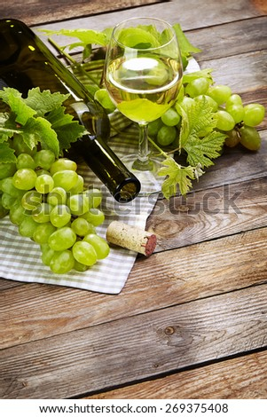 Cheese, a bottle of  wine with grape, walnut  and fig on old wooden cutting board - stock photo