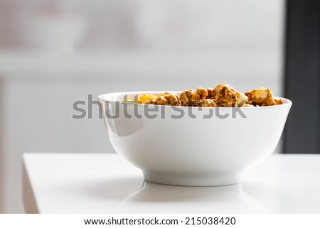 cheese and caramel popcorn in white bowl, side shot - stock photo