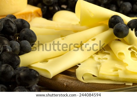 cheese and grape on a cutting board - stock photo