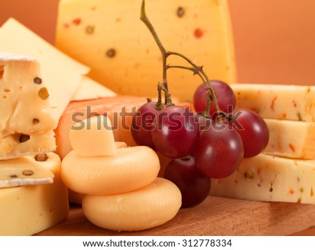 Cheese and grapes still life shot on brown background
