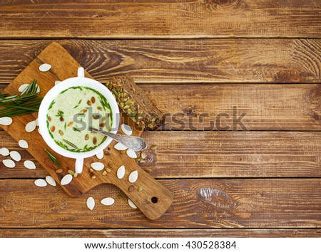 Cheese and greens cream soup with pumpkin sunflower seeds on a wooden background. Foods background - stock photo