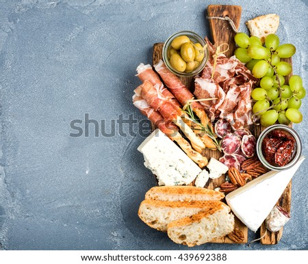Cheese and meat appetizer selection. Prosciutto di Parma, salami, bread sticks, baguette slices, olives, sun-dried tomatoes, grapes and nuts on rustic wooden board over grey concrete textured backdrop - stock photo