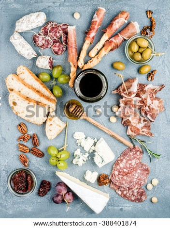 Cheese and meat appetizer selection set. Variety of  cheese, salami, prosciutto, bread sticks, baguette, honey, grapes, olives, sun-dried tomatoes and pecan nuts over grey concrete backdrop, top view - stock photo