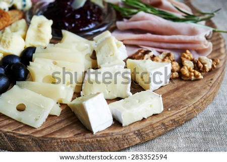 cheese and meat plate with olives and walnuts - stock photo