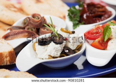 Cheese and olive salad with other mediterranean appetizers - stock photo