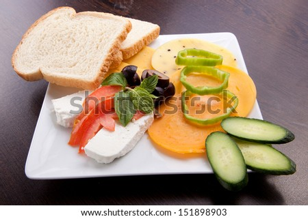 Cheese and olive, tomato platter with vegetable and herbs