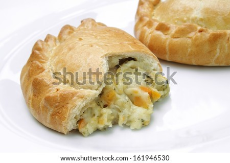 cheese and onion pastie cut open on white plate and background
