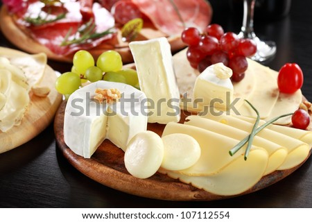 Cheese and salami platter with vegetable and herbs - stock photo
