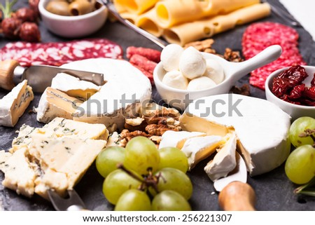 Cheese and salami with olives and nuts on a slate board