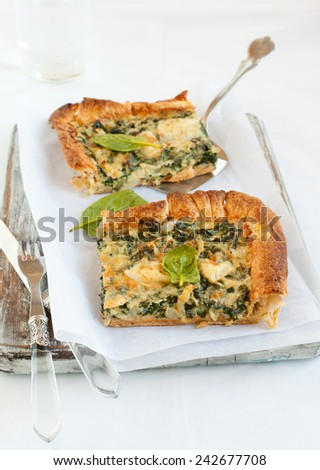 Cheese and spinach quiche pie pieces on a wooden board. Rustic style - stock photo