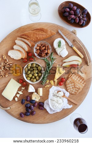 Cheese and wine evening with selection of assorted cheeses fruit nut crackers bread - stock photo